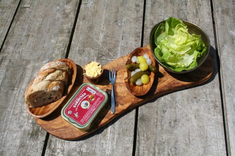 Lunch plankje met sardines, stokbrood, roomboter en sla. de SARDINE WINKEL